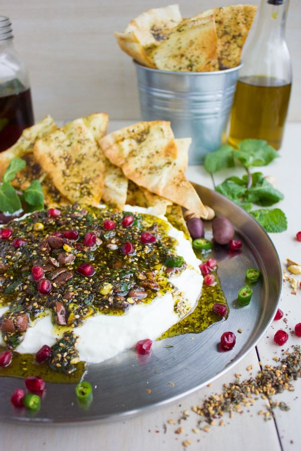 Side view of creamy Labneh Dip with Zaatar Pistachio Mint Olive Topping and pomegranate seeds served on a silver platter with a side of zaatar-dusted pita chips and ice tea.