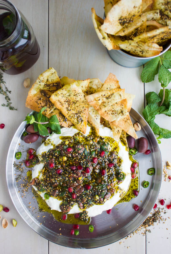 Overhead shot of Labneh Dip with Zaatar Pistachio Mint Olive Topping and pomegranate seeds served on a silver platter with a side of zaatar-dusted pita chips and ice tea.