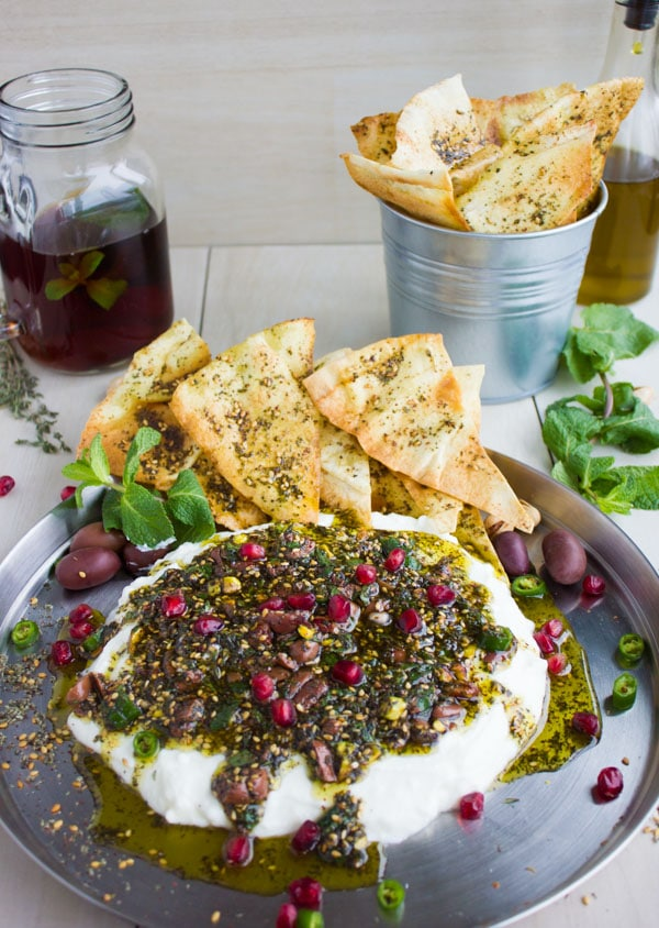 Labneh Dip with Zaatar Pistachio Mint Olive Topping and pomegranate seeds served on a silver platter with a side of zaatar-dusted pita chips and ice tea.