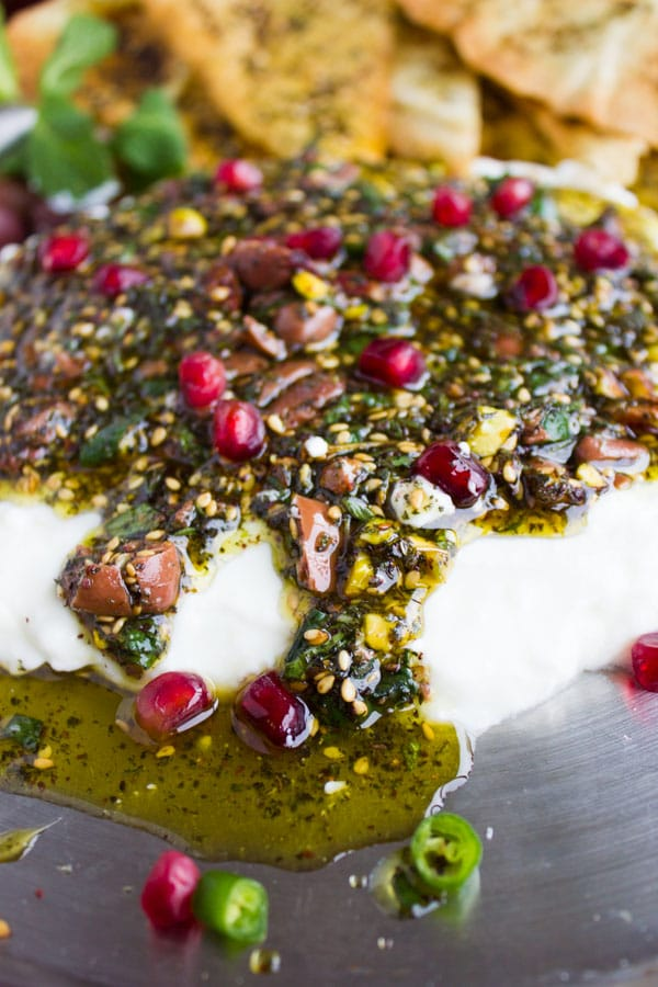 Close-up of Labneh Dip with Zaatar Pistachio Mint Olive Topping running down the sides and a pool of olive oil gathering in front of it.