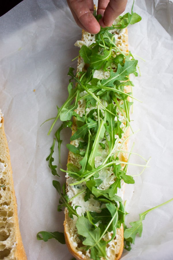 half a baguette sliced open with some arugula on top