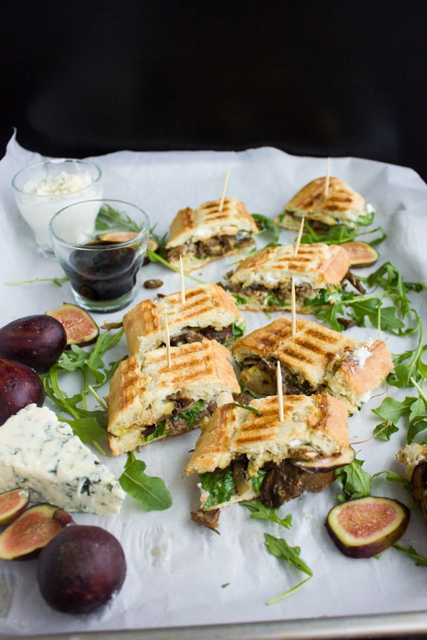 Blue Cheese Philly Steak Sandwich Bites arranged on white parchment paper with some ingredients and a dish with balsamic dip on the side