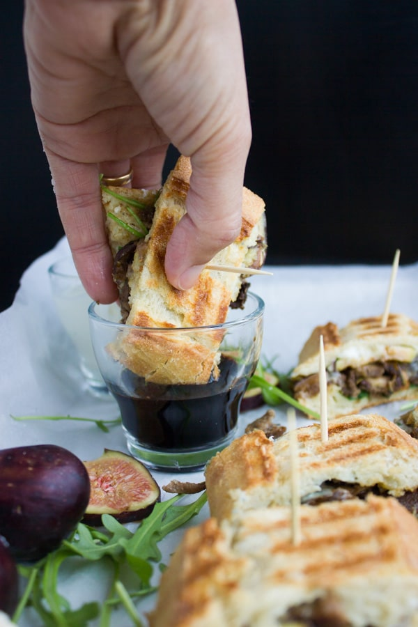 Slice of Blue Cheese Philly Steak Sandwich being dipped into a dish with balsamic dip