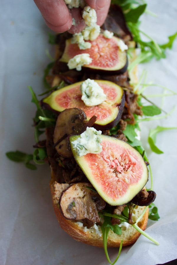blue cheese being sprinkled on top of an open baguette sandwich with steak slices, arugula and fresh figs