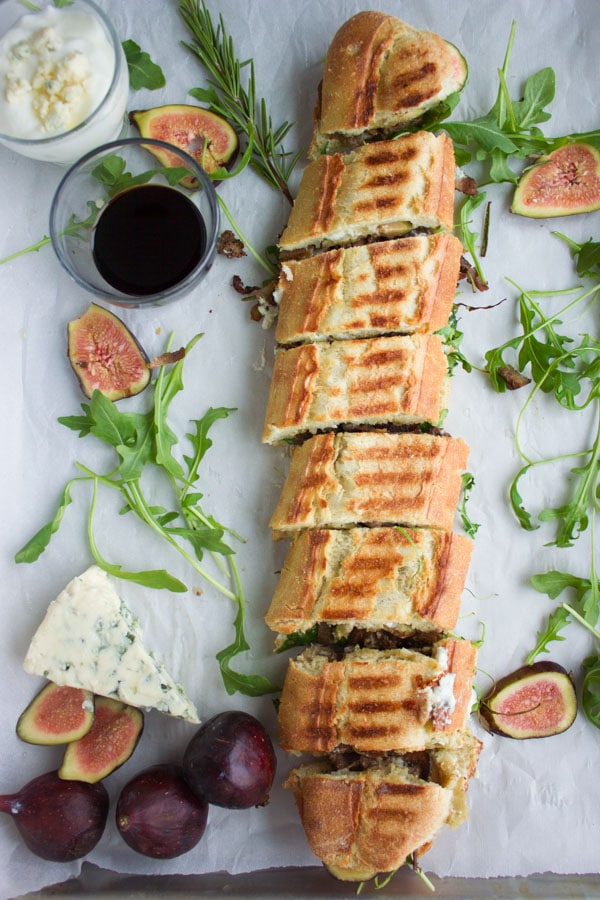 overhead-shot of a filled sandwich baguette cut into slices and whimsically arranged on parchment paper with arugula, figs and a wedge of cheese