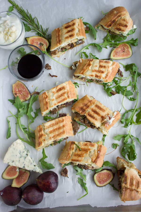 bite-sized pieces of Blue Cheese Philly Steak Sandwich arranged on parchment paper with fresh figs, blue cheese and arugula surrounding them