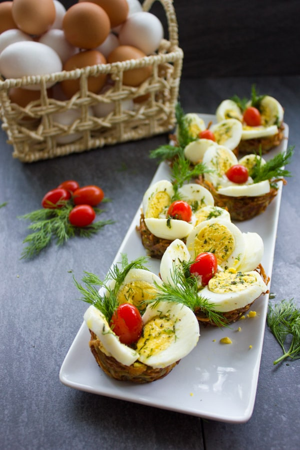 Easter Egg Tart Potato Nests on a rectangular white plate topped with eggs, tomatoes and fresh dill