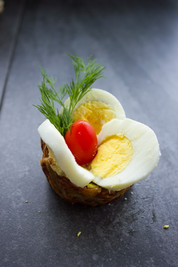potato nests being topped with sliced Easter eggs
