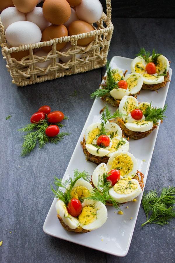 overhead shot of a white rectangular plate with Easter Egg Tart Potato Nests