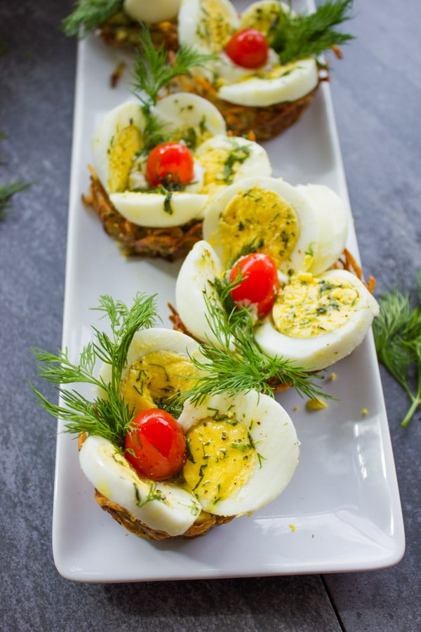 close-up of a rectangular plate with Easter Egg Tart Potato Nests topped wth fresh dill