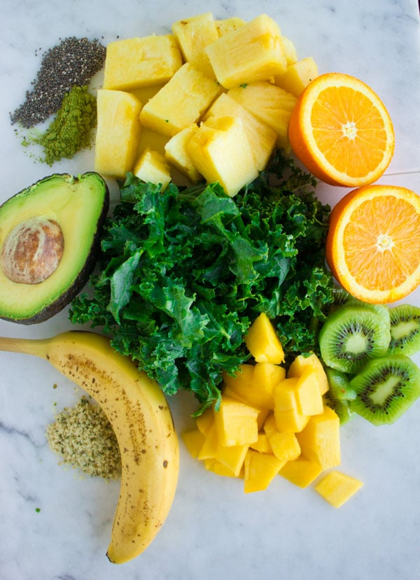smoothie ingredients like kale, pineapple chunks, kiwi slices, banana, half an avocado and mango cubes piled up on a white surface.