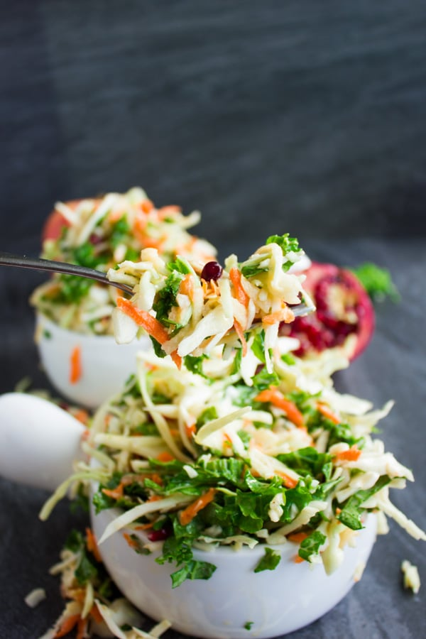 a fork full of coleslaw with kale, grated apples and pomegranate seeds balanced over white bowl filled with more coleslaw.