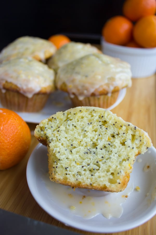 half a Ginger Clementine Lemon Poppy Seed Muffin on a small white plate, revealing the perfect fluffy crumb