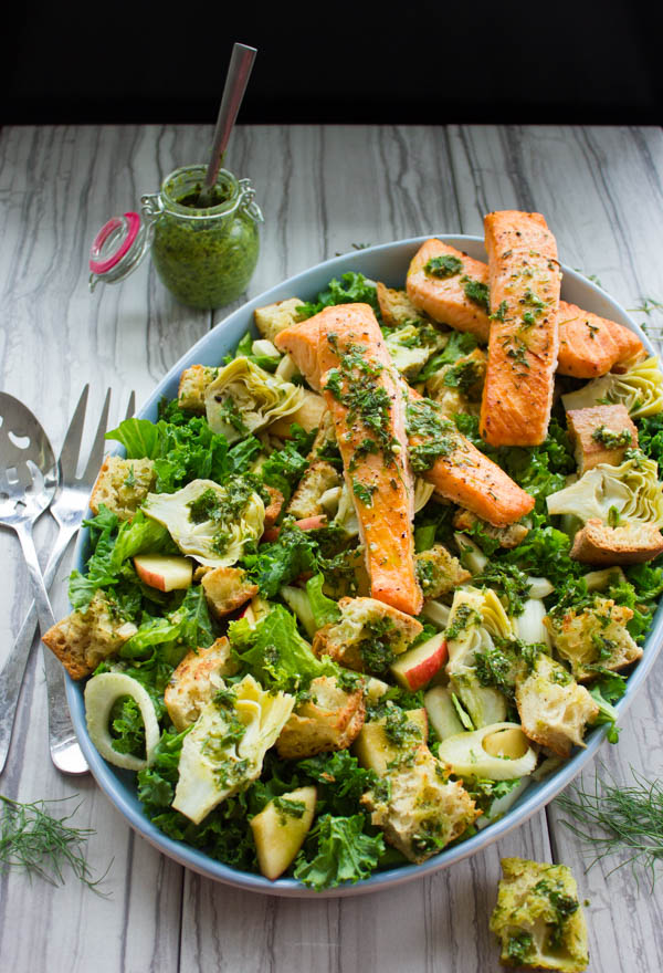 Italian Panzanella Salad With Salmon Strips and Basil Dressing served in a round salad dish on a rustic wood table with a glass of pesto in the background