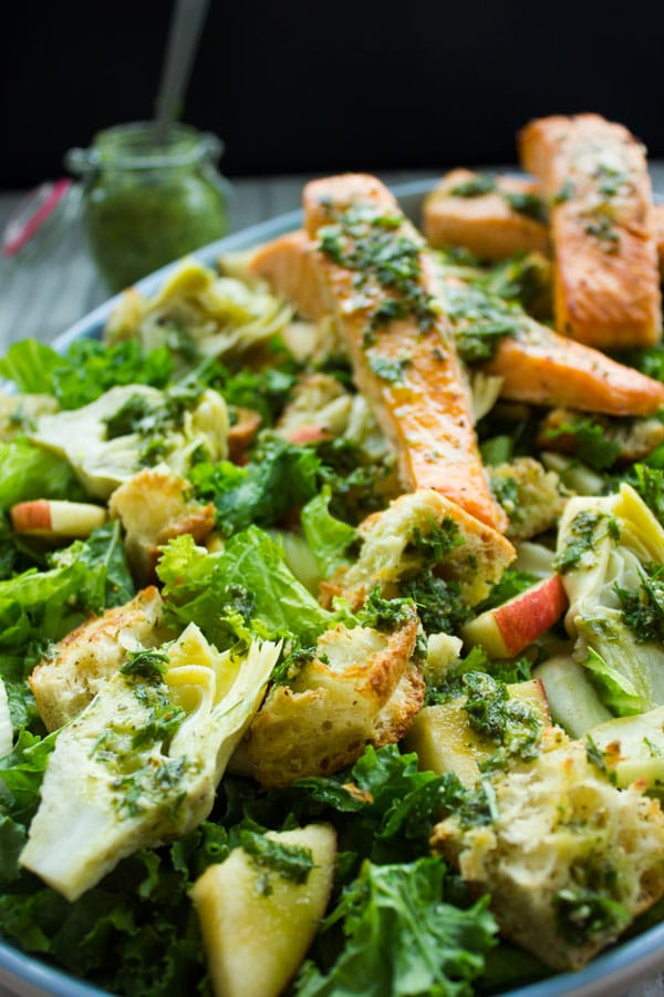 Side view of Italian Panzanella Salad With sliced apples, fennel, salmon strips and Basil Dressing served in a round salad dish on a rustic wood table with a glass of pesto in the background