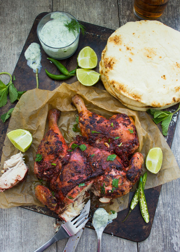 overhead of Quick Roast Tandoori Chicken on a black platter with yogurt dip and naan bread on the side