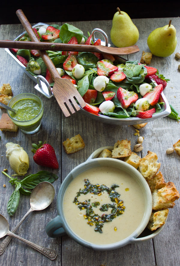 a bowl with pesto-topped artichoke soup in front of a boat-shaped bowl filled with Strawberry Spinach Salad.