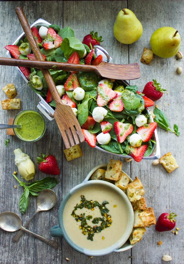 Strawberry Spinach Salad served in a boat-shaped silver bowl next to a bowl with Artichoke Soup and croutons.