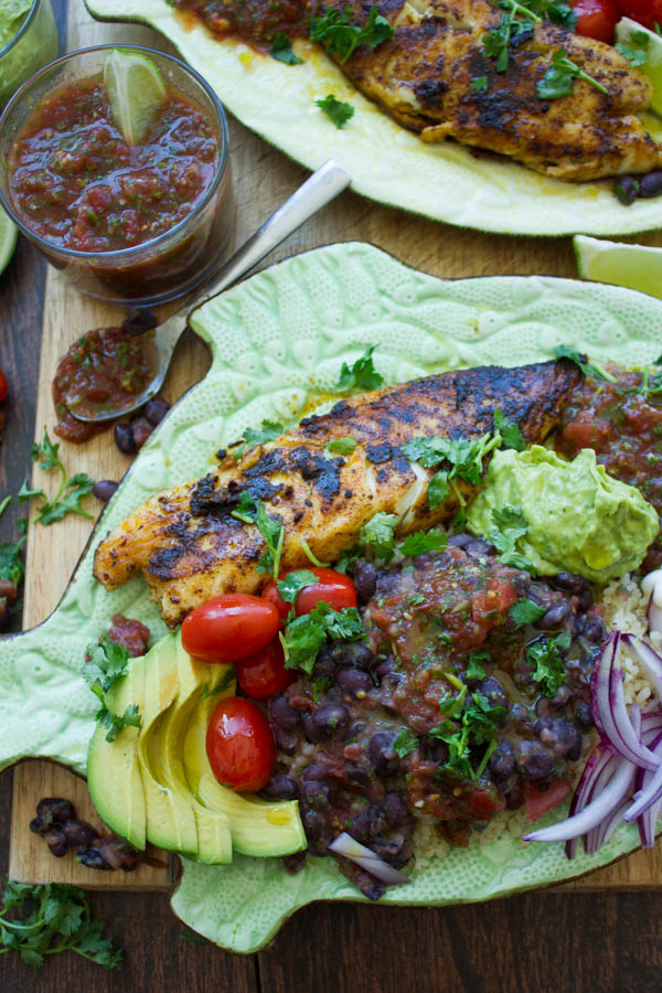 overhead of pan-fried tilapia fish fillets crusted with Mexican spices and served with black beans, guacamole and salsa on a fish shaped plate