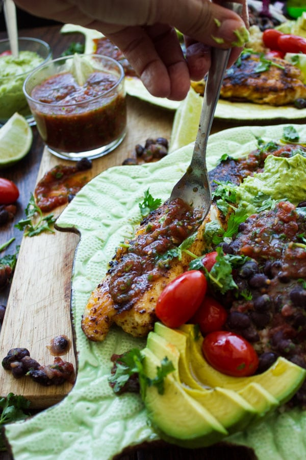 salsa being drizzled on top of spice crusted pan-fried tilapia fillets with black beans and guacamole on the side