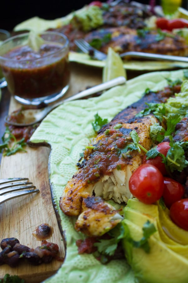 close up of Mexican pan-fried tilapia fillet crusted with spices served next to sliced avocado and a dish with homemade salsa