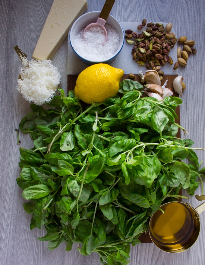 Ingredients on a cutting board: parmesan cheese, salt, pistachios, lemon, basil, spinach, olive oil.