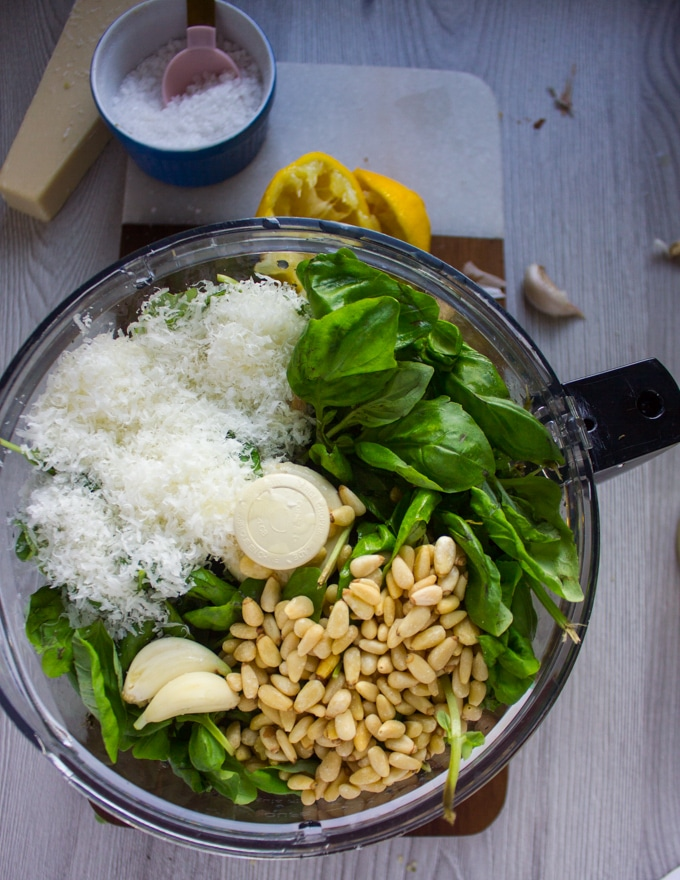 Ingredients in a food processor, showing: basil, parmesan, nuts, garlic.