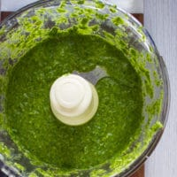 all ingredients for pistachio pesto in a food processor bowl blended and ready