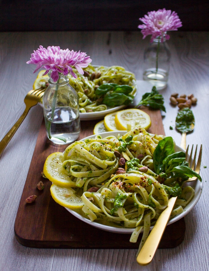 side view of a pesto pasta plate with a frok, some fresh basil and crunchy pistachios on top