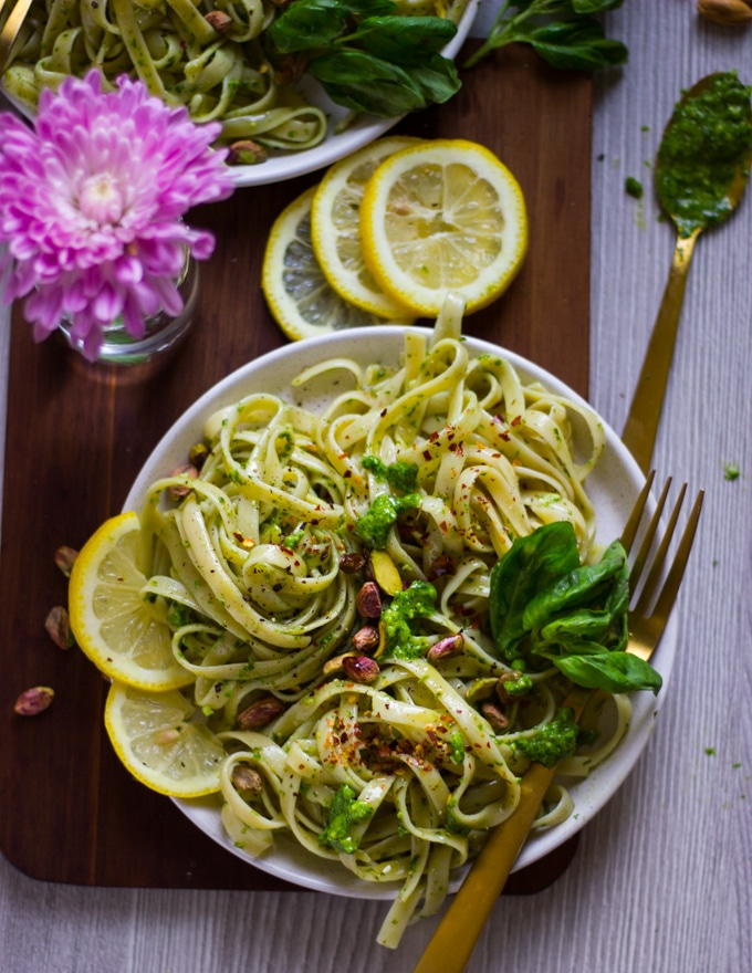 a bowl of pesto pasta with lemon slices and some fresh basil
