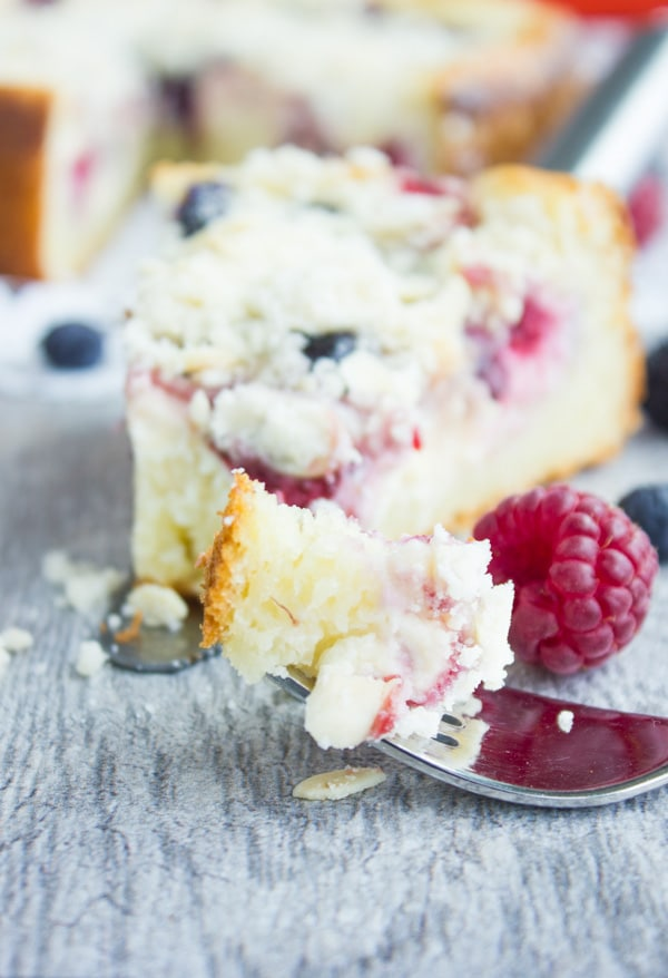 close-up of a fork-full of Cheesecake Streusel Raspberry Cake and a slice of cake in the background