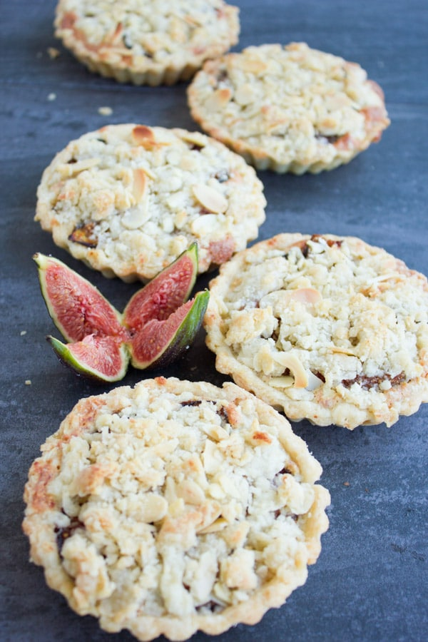 Individual Fig Almond Frangipane Tarts arranged on a rustic dark tabletop with a quartered fresh fig in the background