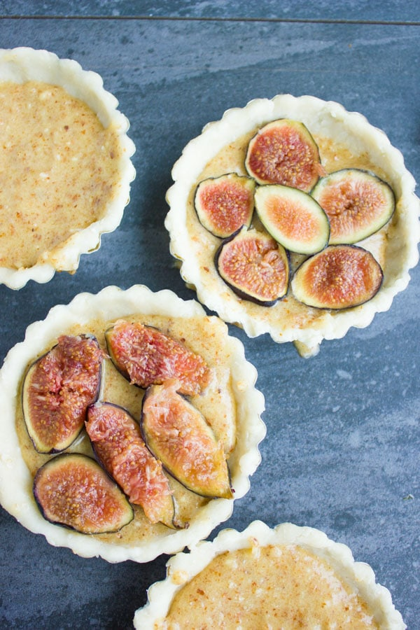 almond frangipane tarts being topped with fresh fig slices