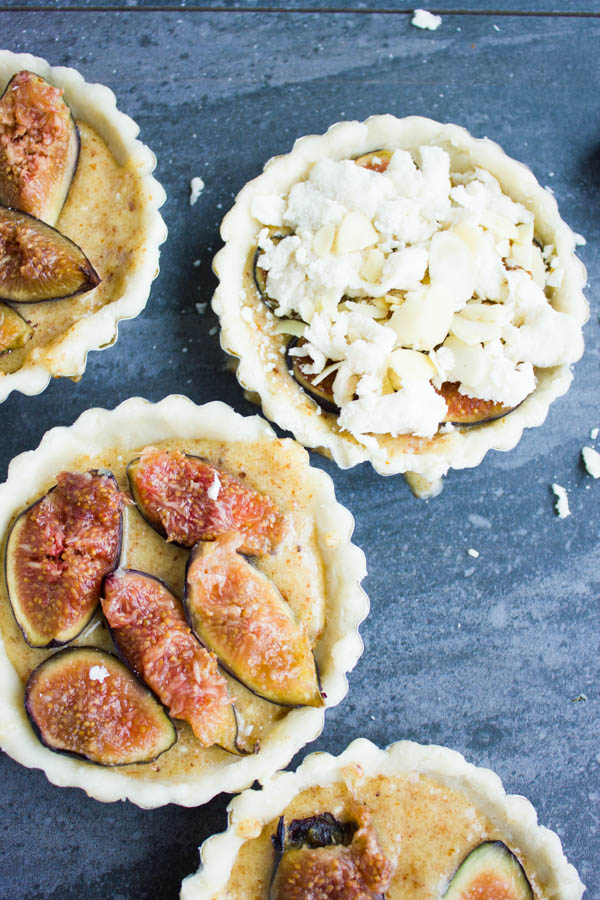 almond frangipane tarts being topped with fresh fig slices and almond streusel topping