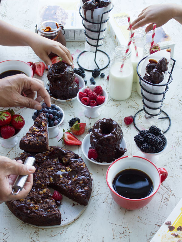 a display of Baked Double Chocolate Glazed Donuts, donut holes and a brownie cake on a table arranged with glasses of milk and bowls filled with fresh berries
