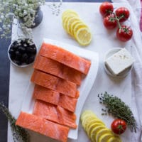 Ingredients for Baked Salmon with Greek Dressing: fish, tomatoes, lemon, feta, olives, herbs.