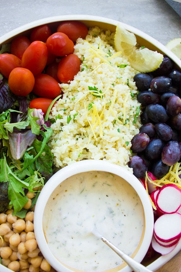 close-up of a white bowl filled with lemon cauliflower rice salad, grapes, cocktail tomatoes, chickpeas, lettuce and radish slices with a small round dish with dressing nestled in between the ingredients.
