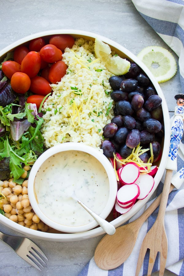 a white bowl filled with lemon cauliflower rice, grapes, cocktail tomatoes, chickpeas, lettuce and radish slices with a small round dish with dressing nestled in between the ingredients.