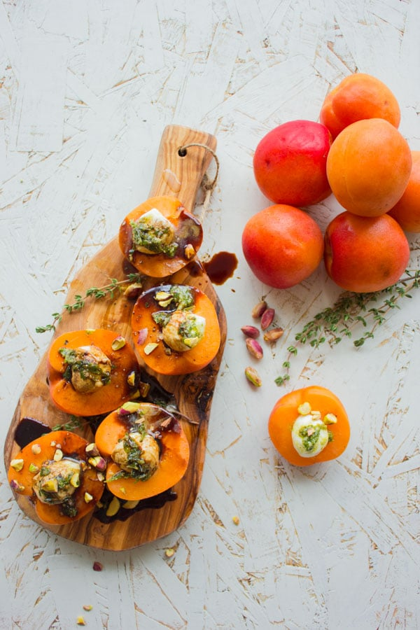 overhead shot of mozzarella stuffed apricots on a wooden board