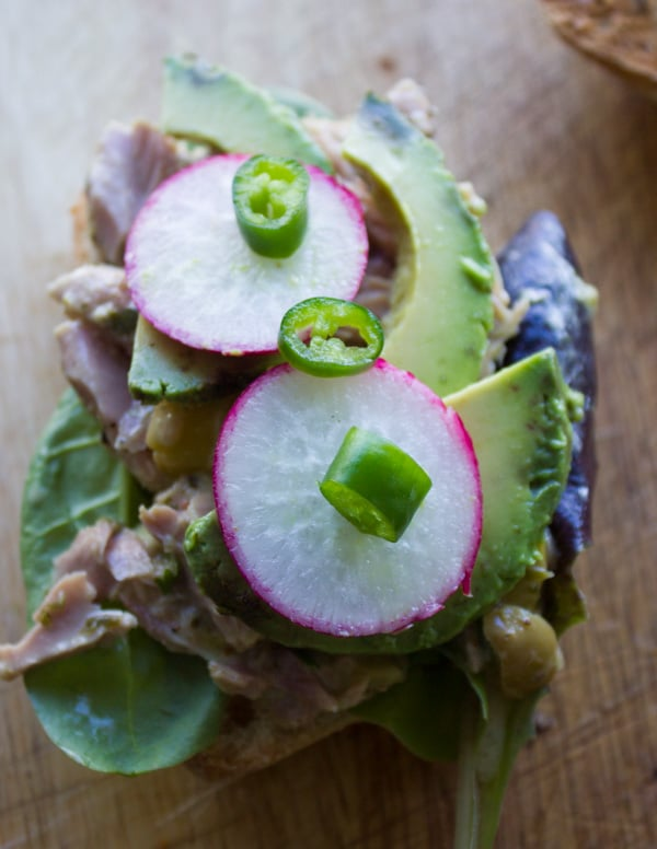 an open tuna sandwich topped with radishes, avocado slices and green onions