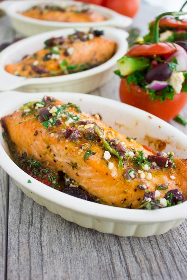 Baked Salmon With Greek Dressing served in individual casseroles with a salad stuffed tomato on the side