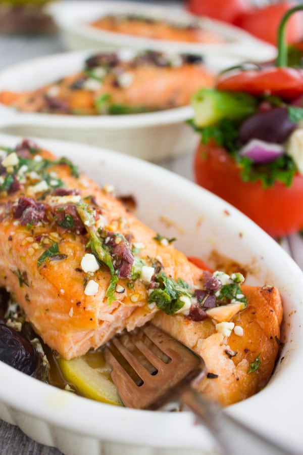a fork tucking into a Baked Salmon Fillet covered with Greek Dressing