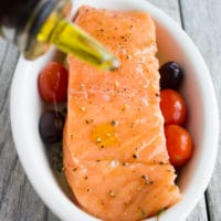 a raw salmon fillet in a small white casserole dish being drizzled with olive oil