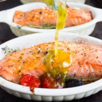Freshly Baked Salmon Fillets being drizzled with Greek Dressing