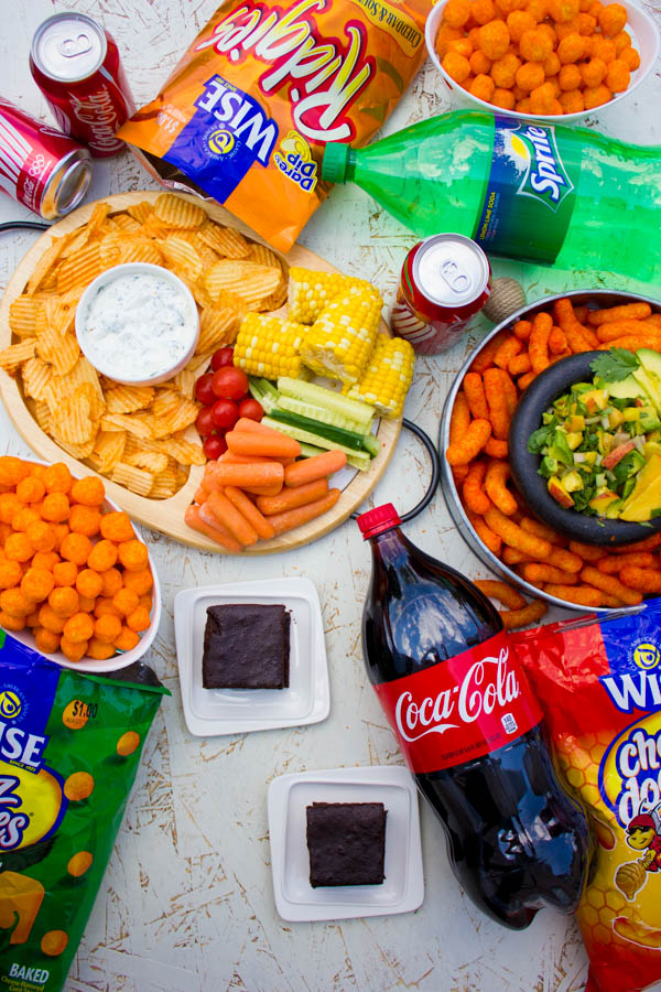 Overhead shot of Tailgate Party Food, like different dips, chips and brownies, arranged on a table