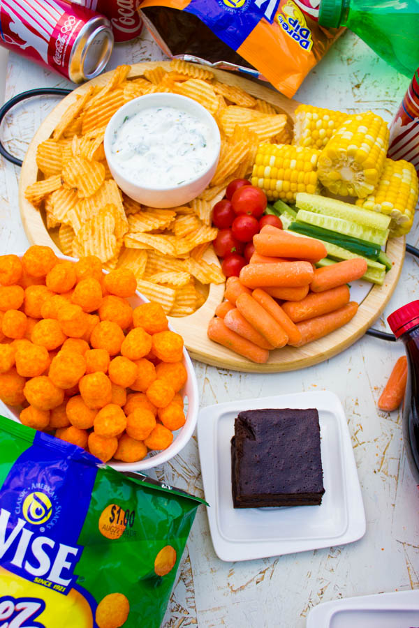 a small dish of herb yogurt dip surrounded by chips and veggie sticks as well as a bowl of cheese pops and a plate with coca cola brownies on a table