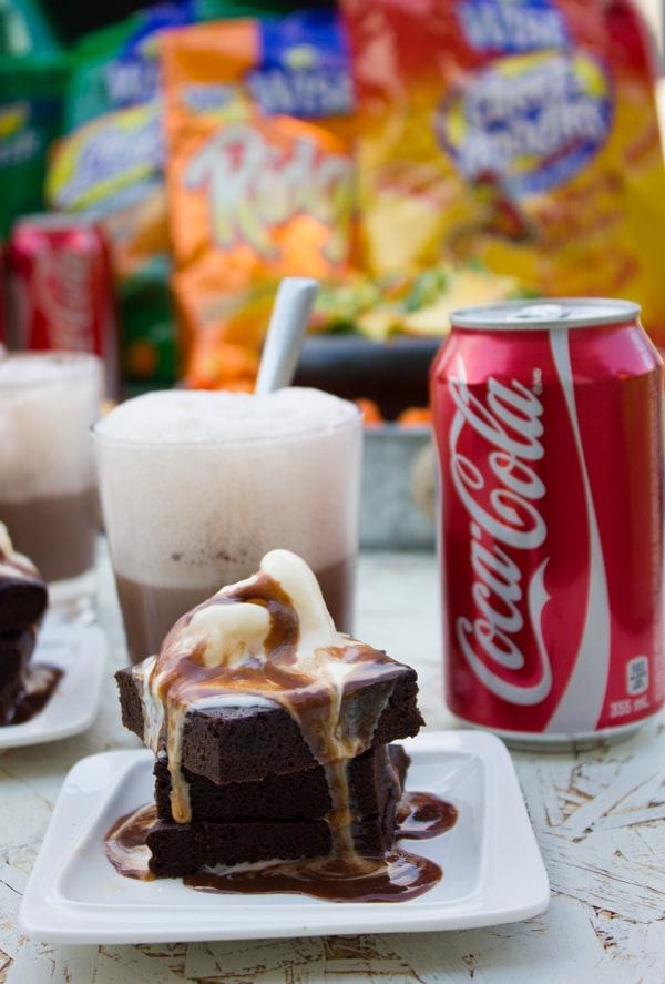 a plate with stacked coca-cola brownies topped with a scoop of ice cream and chocolate sauce with ice cream floats and chips bags in the background
