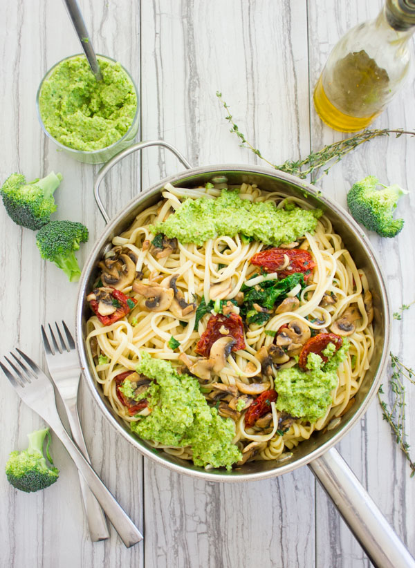 overhead shot of a skillet with mushroom and tomato pasta topped with broccoli pesto