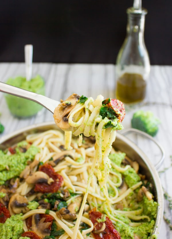 a fork full of broccoli pesto pasta with sun-dried tomatoes, mushrooms and olives