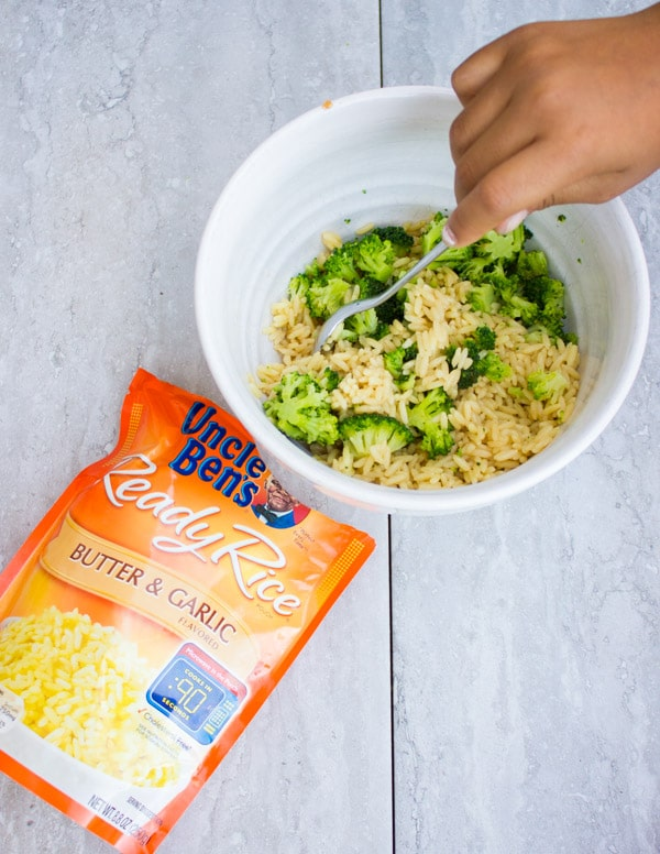 rice being added to broccoli in a white bowl to make a filling